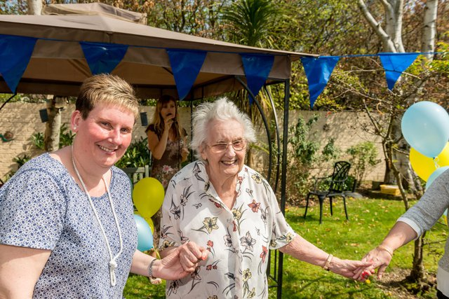 Amberley Lodge Nursing Home in Purley resident and carer holding hands in garden