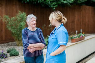 Carer and resident in the garden at Oxendon House