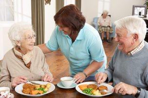 SureCare Home Care in Wolverhampton elderly couple eating dinner with carer