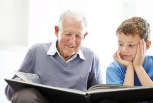 Elder Home Care elderly man reading book with boy