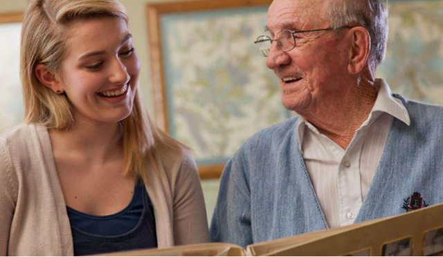 Home Instead Senior Home Care in Reading elderly man reading with younger lady