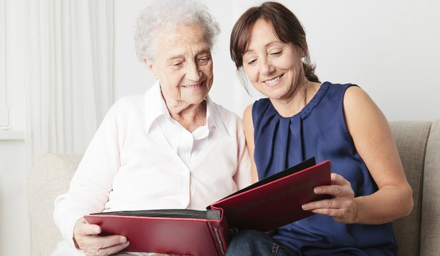 Swift House Home Care in Solihull elderly lady reading book with younger lady
