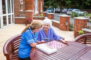 Resident outside with carer at St Andrew's Nursing and Care Home
